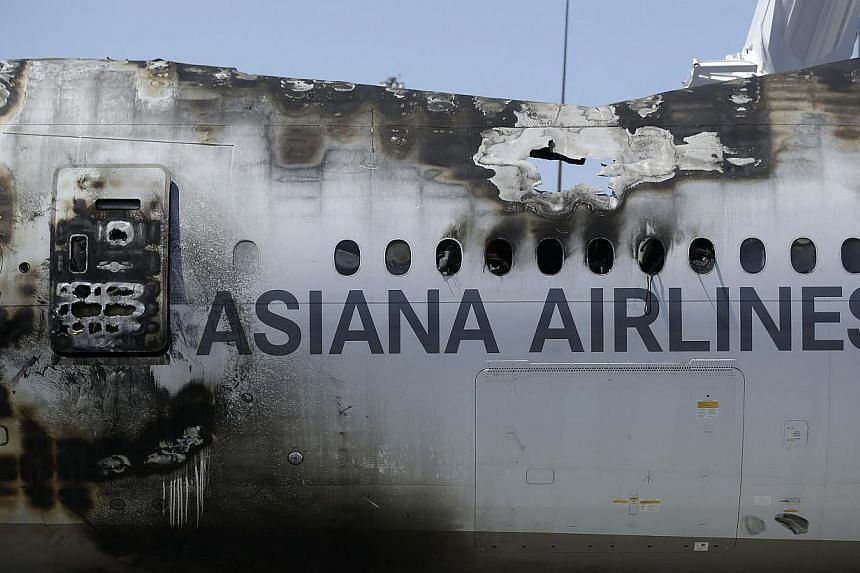 The wreckage of Asiana Flight 214, which crashed on Saturday, July 6, 2013, seen at San Francisco International Airport, in San Francisco, Friday, July 12, 2013. The third girl who died in the aftermath of the crash is a Chinese national, a spokesman
