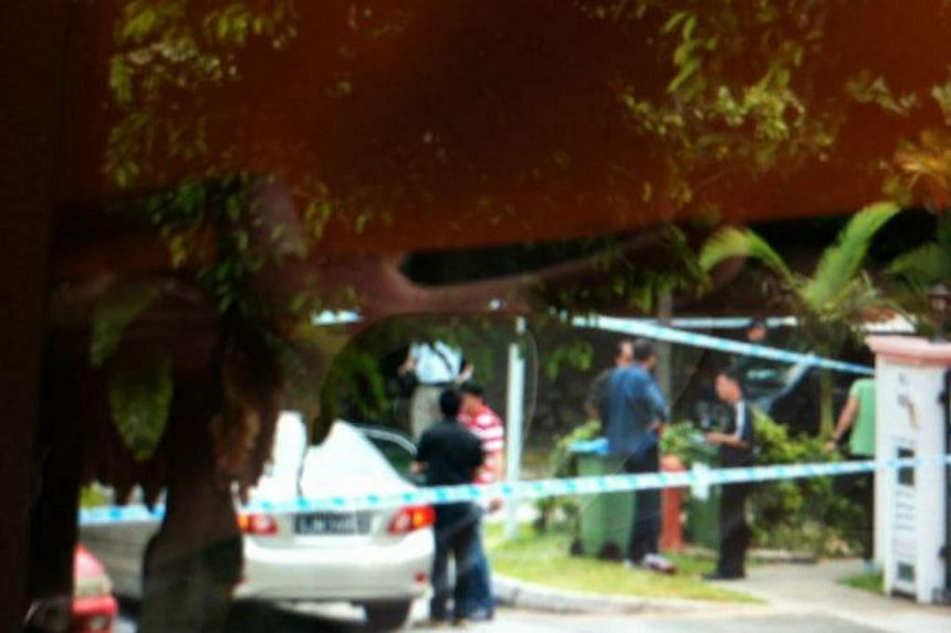 The Kovan murder suspect, 34-year-old Singapore policeman Iskandar Rahmat, was taken by police to the crime scene at Hillside Drive at about 2.15pm on Saturday. -- ST PHOTO: DESMOND FOO