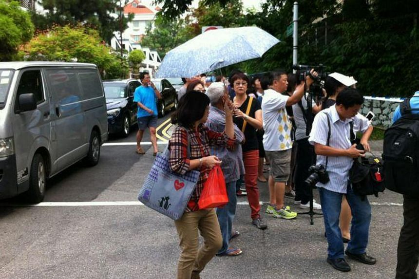 People gather along Hillside Drive on Saturday, July 13, 2013. The Kovan murder suspect, 34-year-old Singapore policeman Iskandar Rahmat, was taken by police to the crime scene at Hillside Drive at about 2.15pm on Saturday. -- ST PHOTO: DESMOND FOO