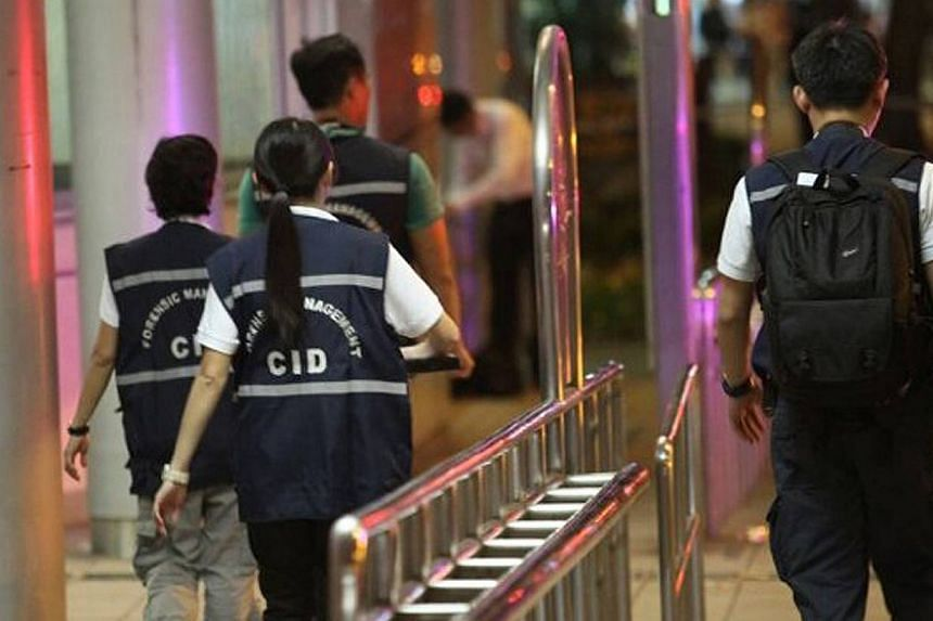Police officers walk outside Kovan MRT on July 10, 2013, after two bodies were found in Kovan about a kilometre from each other. A 34-year-old man was arrested on Friday at 11.30pm in connection with the double murders at Kovan, police said in a stat