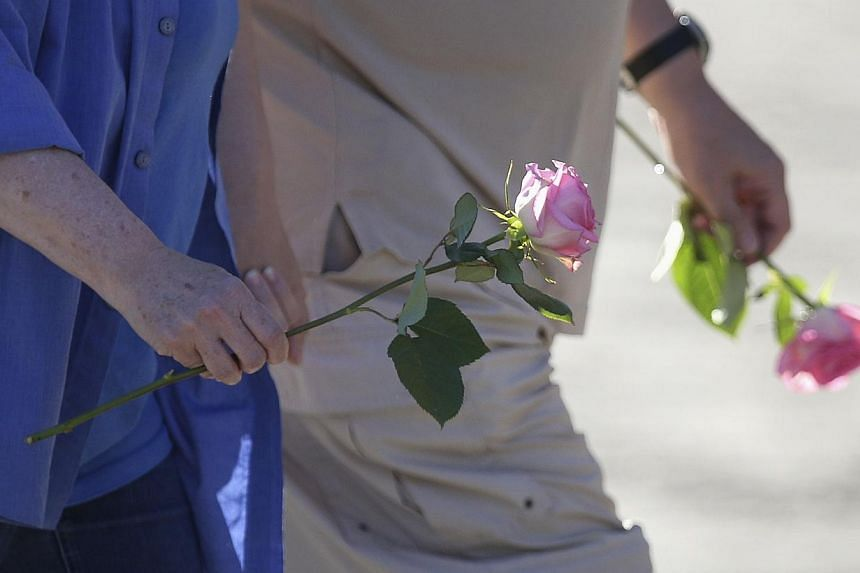 People bring roses as they arrive at Sainte-Agnes church in Lac-Megantic, Quebec on July 12, 2013. Shell-shocked residents of Lac-Megantic took small steps on a long path back to normalcy on Friday as they returned to homes and businesses just a shor