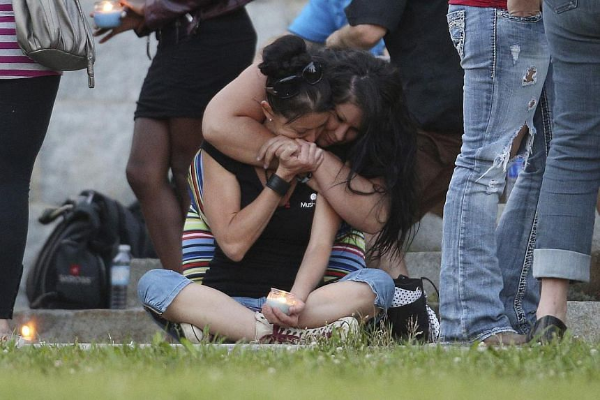 A woman consoles her friend during a candlelight vigil at the Sainte-Agnes church in Lac-Megantic, Quebec on July 12, 2013. Shell-shocked residents of Lac-Megantic took small steps on a long path back to normalcy on Friday as they returned to homes a