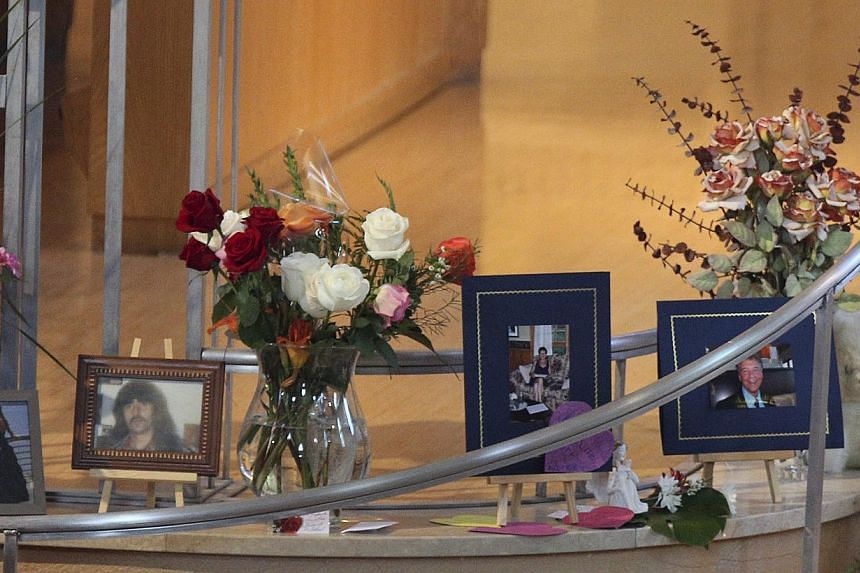 Pictures and flowers are pictured on a memorial at the Sainte-Agnes church in Lac Megantic, on July 13, 2013. The crude oil freight train that derailed and blew up in the small town of Lac-Megantic early on Saturday morning was traveling far too fast
