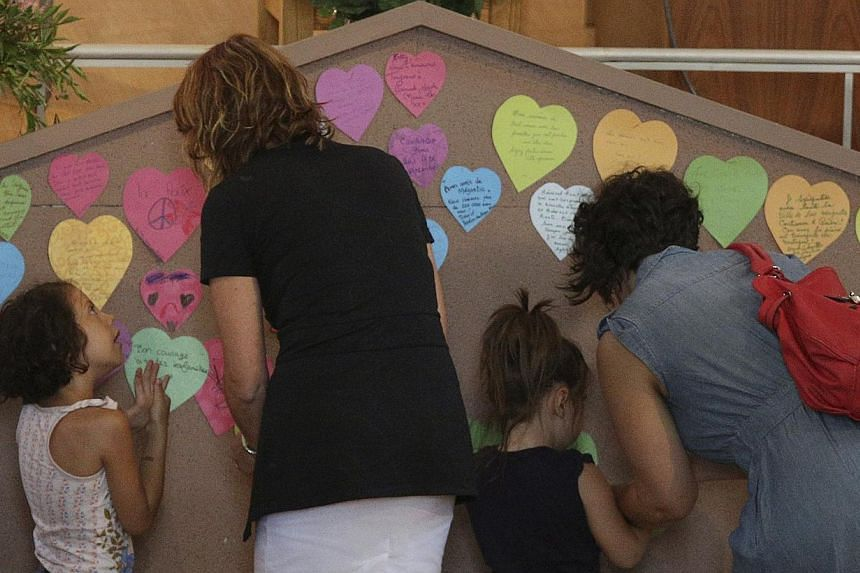 People place paper hearts on a memorial at the Sainte-Agnes church in Lac Megantic, on July 13, 2013. The crude oil freight train that derailed and blew up in the small town of Lac-Megantic early on Saturday morning was traveling far too fast when it