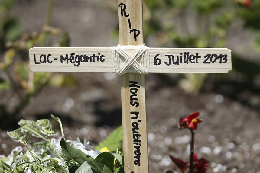 """A wooden cross is pictured in front of Sainte-Agnes church in Lac Megantic, on July 13, 2013. The inscription reads """"RIP, Lac Megantic July 6, 2013, We will never forget"""". The crude oil freight train that derailed and blew up in the small town of Lac"""
