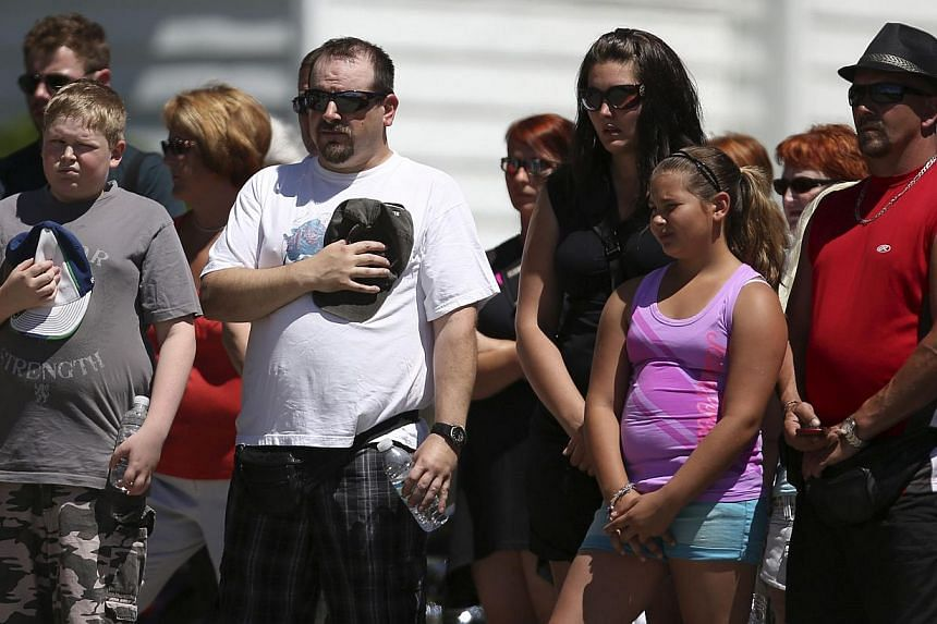 People observe a minute of silence the Sainte-Agnes church in Lac Megantic, on July 13, 2013. The crude oil freight train that derailed and blew up in the small town of Lac-Megantic early on Saturday morning was traveling far too fast when it went of