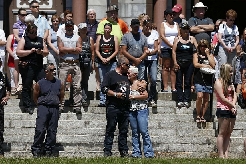 A couple mourns while the bells ring at the Sainte-Agnes church in Lac Megantic, on July 13, 2013. The crude oil freight train that derailed and blew up in the small town of Lac-Megantic early on Saturday morning was traveling far too fast when it we