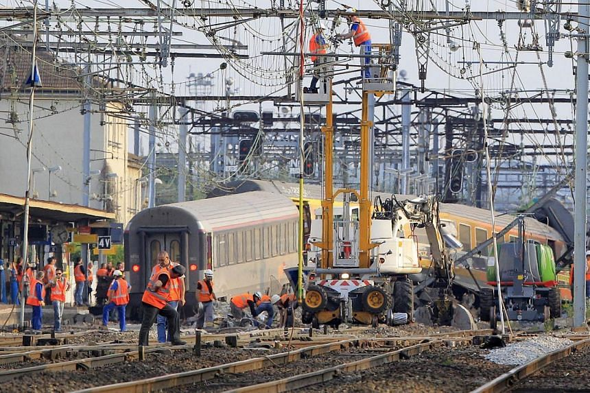 French railway employees and rescue workers inspect the wreckage of a derailed intercity train at the Bretigny-sur-Orge station near Paris on July 13, 2013. A train derailment near Paris that killed six people was caused by a fault in the tracks, Fra