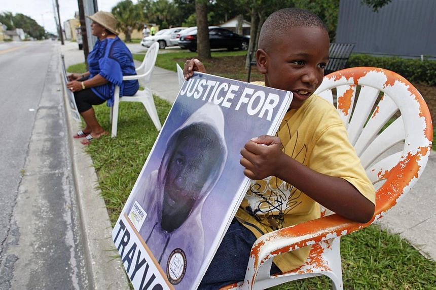 Antonio McVay, 8, holds a sign in front of his home in the Goldsboro Historical neighborhood, Saturday, July 13, 2013, in Sanford, Fla., while residents wait for word on the verdict in the George Zimmerman trial. Zimmerman has been charged with the 2