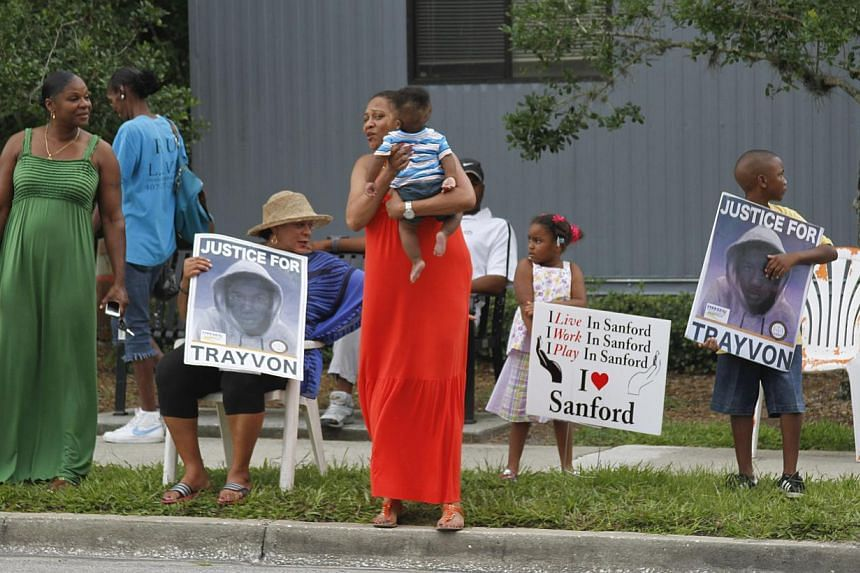 Residents of the Goldsboro historical neighborhood gather and hold signs supporting Travon Martin while waiting for word on the verdict in the trial of George Zimmerman, Saturday, July 13, 2013, in Sanford, Fla. Zimmerman is charged in the 2012 shoot