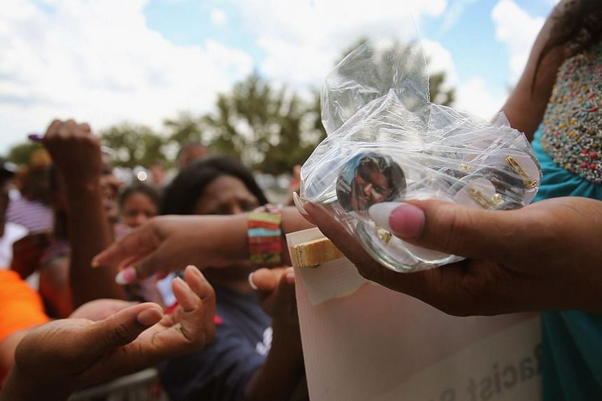 A demonstrator passes out buttons with a picture of Trayvon Martin during a protest in front of the Seminole County Criminal Justice Center where a jury is deliberating in the trial of George Zimmerman on July 13, 2013 in Sanford, Florida. Zimmerman,