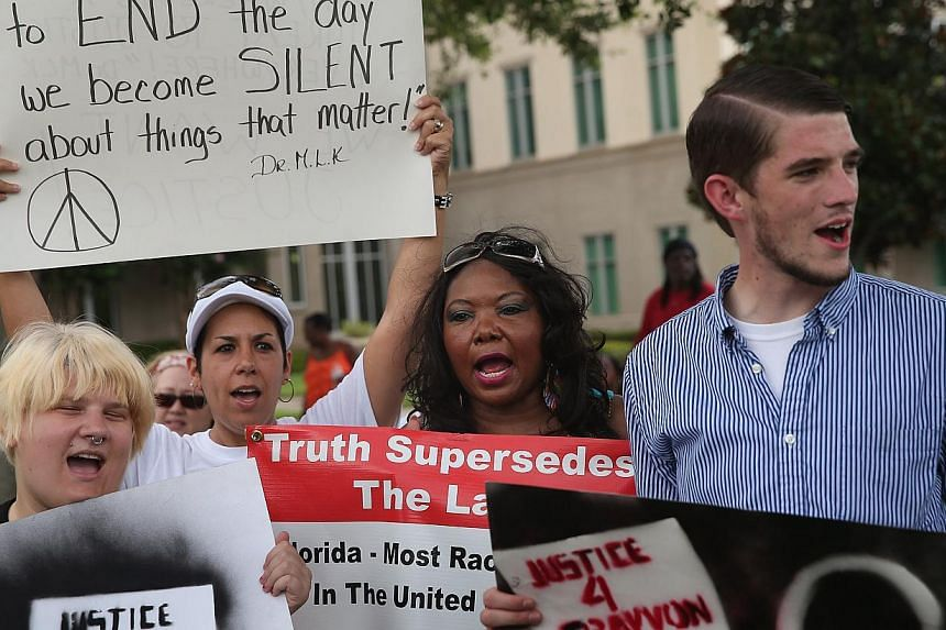 Demonstrators protest in front of the Seminole County Criminal Justice Center where a jury is deliberating in the trial of George Zimmerman on July 13, 2013 in Sanford, Florida. Zimmerman, a neighborhood watch volunteer, is on trial for the February
