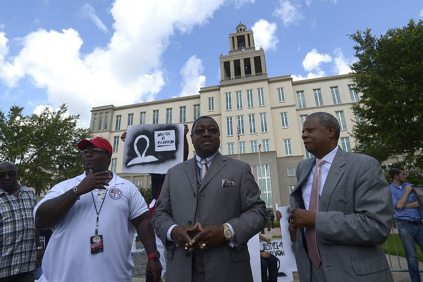 Pastor Monzell Ford, second from left, Dr. L. Ronald Durham, center, and Pastor John Long III, all of Daytona Beach, Fla., call for peace during the George Zimmerman trial outside the Seminole County Courthouse in Sanford, Fla., Saturday, July 13, 20