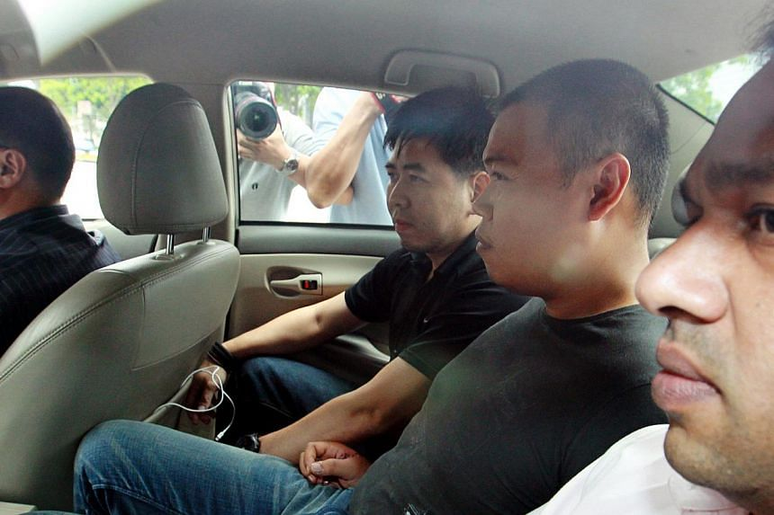 Iskandar Rahmat (second from right) arrives at the Police Cantonment Complex yesterday after being brought back to Singapore from Johor, where he was arrested on Friday night. He met murder victim Tan Boon Sin at least once, when the workshop owner r