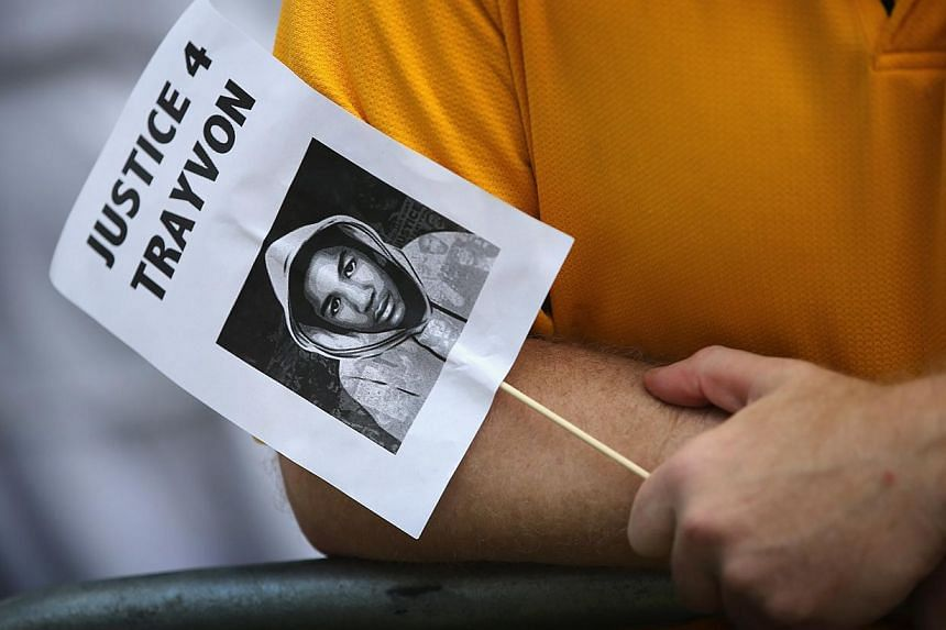 A demonstrator holds a sign with the likeness of Trayvon Martin while protesting in front of the Seminole County Criminal Justice Center where a jury is deliberating in the trial of George Zimmerman on July 13, 2013 in Sanford, Florida. Zimmerman, a