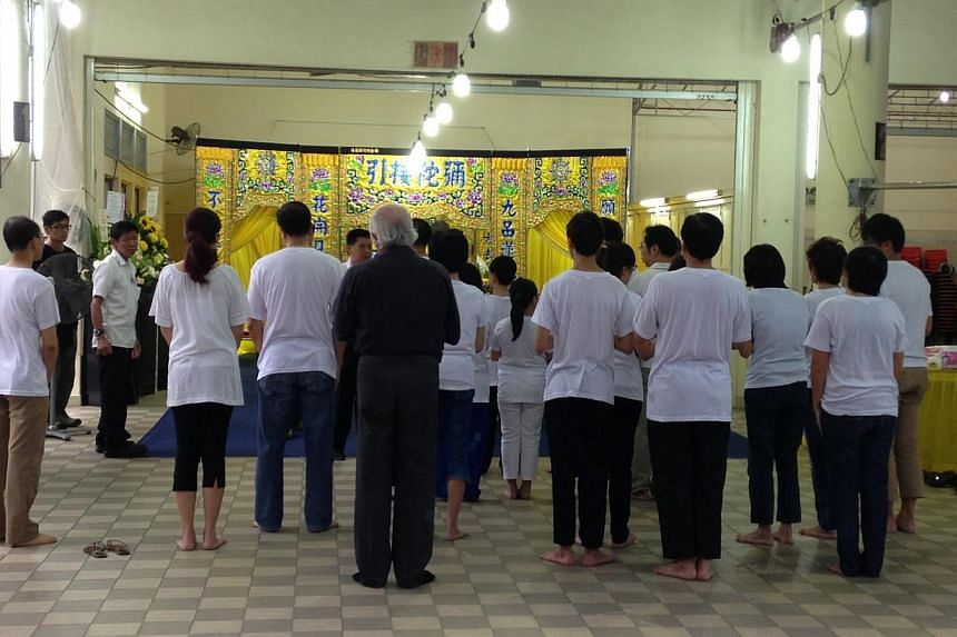 Opening funeral rites for victims of the Kovan double murder began on the evening of Sunday, July 14, 2013, a few hours after the bodies of Mr Tan Boon Sin, 67, and his son Tan Chee Heong, 42, were collected by their family earlier in the day. -- ST