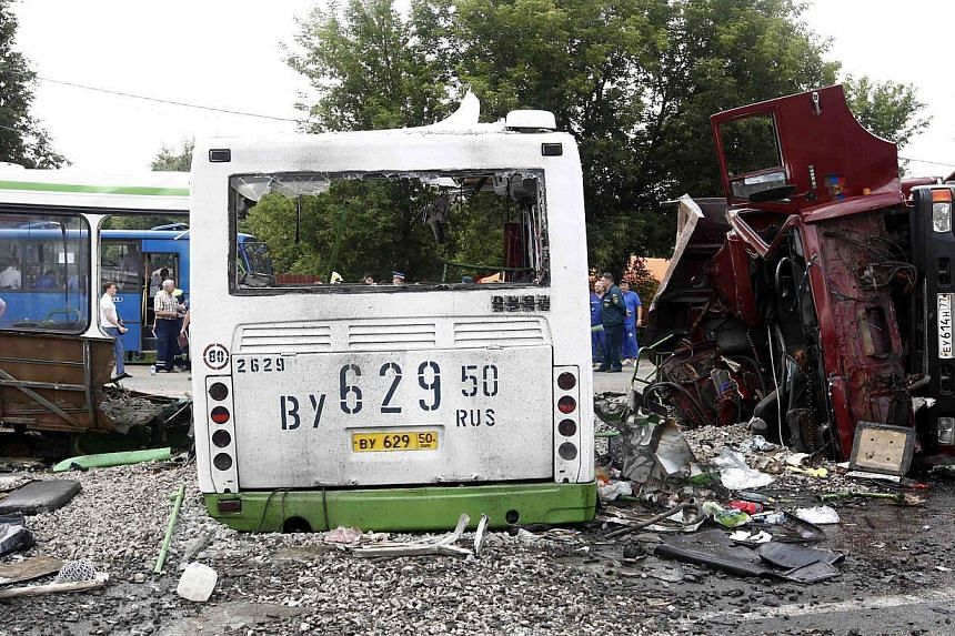 Members of the emergency services work at the scene of a collision between a bus and a truck outside Moscow on Saturday, July 13, 2013. Russian investigators on Sunday interrogated the hospitalised driver of a truck that ploughed into a pac