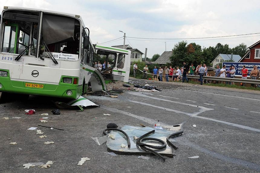 People check the crash scene near the village of Oznobikhino outside Moscow on Saturday, July 13, 2013. Russian investigators on Sunday interrogated the hospitalised driver of a truck that ploughed into a packed passenger bus outside Moscow killing 1
