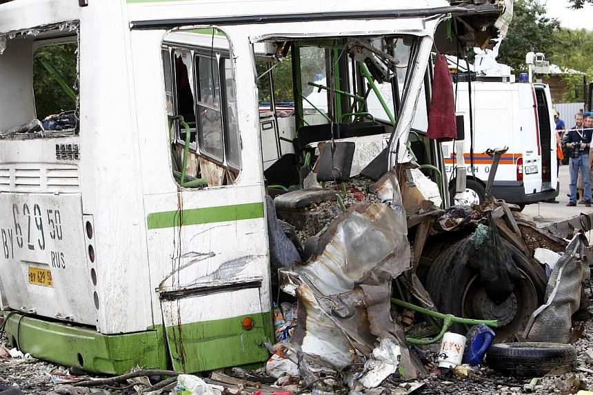 The wreckage of a bus is seen as members of the emergency services and police work at the scene of a collision between the bus and a truck outside Moscow on Saturday, July 13, 2013. Russian investigators on Sunday interrogated the hospitali