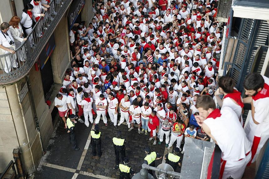 Participants wait for the start of the last bull run of the San Fermin Festival in Pamplona, northern Spain on Sunday, July 14, 2013. A 23-year-old Australian woman was gored in the chest on the final day of Spain's San Fermin week-long bull-running