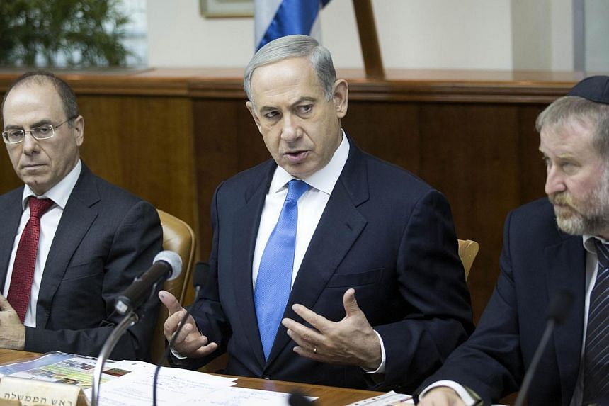 """Israel's Prime Minister Benjamin Netanyahu (centre) attends the weekly cabinet meeting in Jerusalem on July 14, 2013. Iran is moving """"closer and closer"""" to building a nuclear weapon and Israel may have to act before the United States does, Israel's P"""
