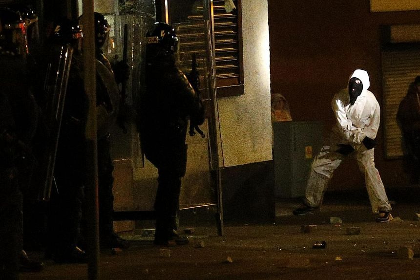 A loyalist rioter attacks riot police in the Woodvale area of north Belfast, Northern Ireland, on Monday, July 15, 2013. Northern Ireland's First Minister Peter Robinson on Sunday called for peace as riots erupted in Belfast for the third night runni