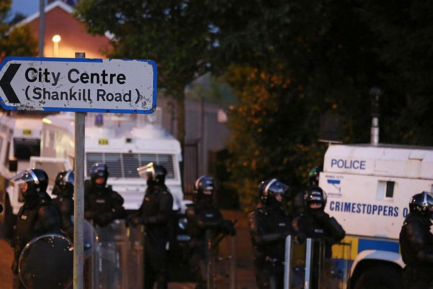 Police stand guard in the Woodvale Road area of North Belfast on July 14, 2013, the third night of unrest after an Orange Parade was blocked from marching past the Nationalist Ardoyne area in Belfast on Friday.-- PHOTO: REUTERS