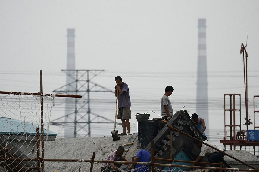 A group of Chinese workers rest on the roof of a building at a construction site in Beijing on July 14, 2013. China's economic growth dropped to 7.5 percent in the second quarter of this year, analysts predicted in an AFP survey ahead of fresh GDP fi