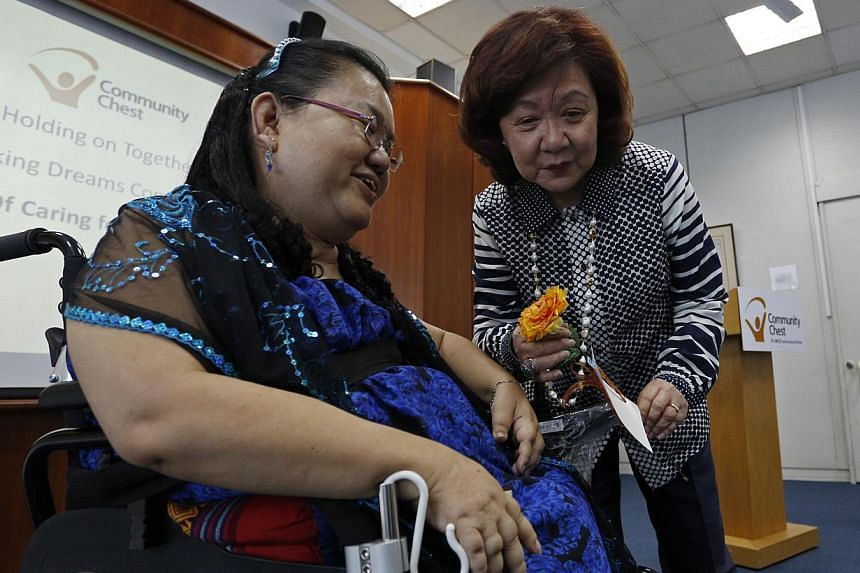 Chairman of Community Chest, Ms Jennie Chua (right) receives a specially-made flower from Ms Mary Kaw, 54, a Community Chest beneficiary and resident from the Singapore Cheshire Home during the Community Chest Fund-Raising Launch at the Society of Ph