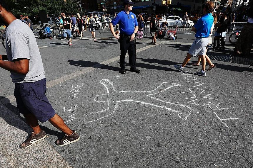 A police officer stands by a chalk outline honoring Trayvon Martin at a rally for Martin in Union Square in Manhattan on July 14, 2013 in New York City. Hundreds protested in New York on Sunday against the acquittal of neighbourhood watchman Geo