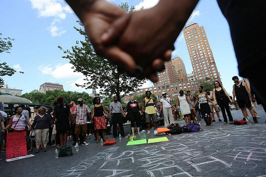 People hold hands in a circle at a rally honoring Trayvon Martin at Union Square in Manhattan on July 14, 2013 in New York City. Hundreds protested in New York on Sunday against the acquittal of neighbourhood watchman George Zimmerman, a day aft