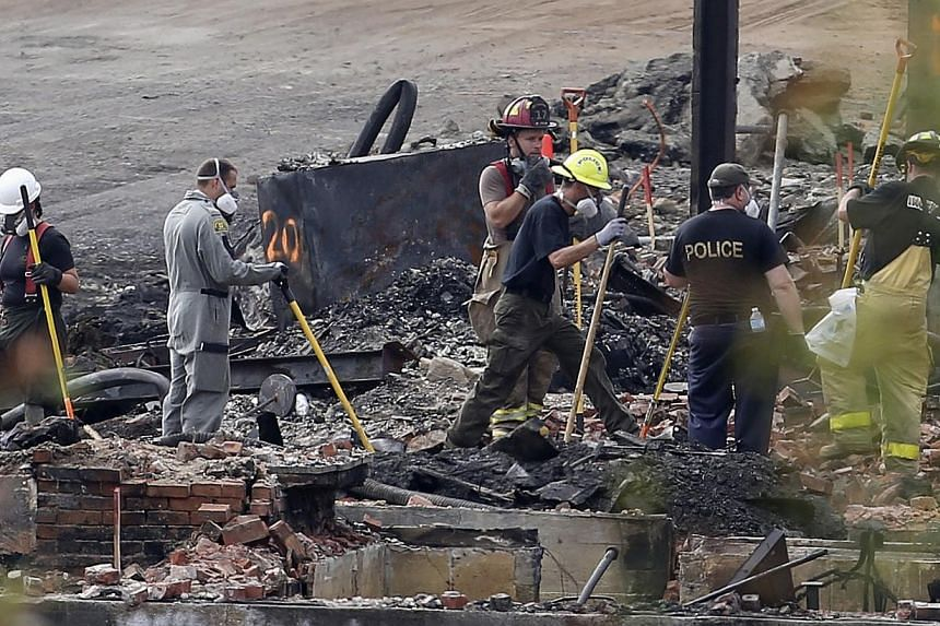 Firefighters and forensic experts work on the wreckage in Lac-Megantic, July 14, 2013. Two more bodies were found on Sunday in downtown Lac-Megantic, the Quebec town devastated when an oil tanker train derailed and exploded, bringing the body count t