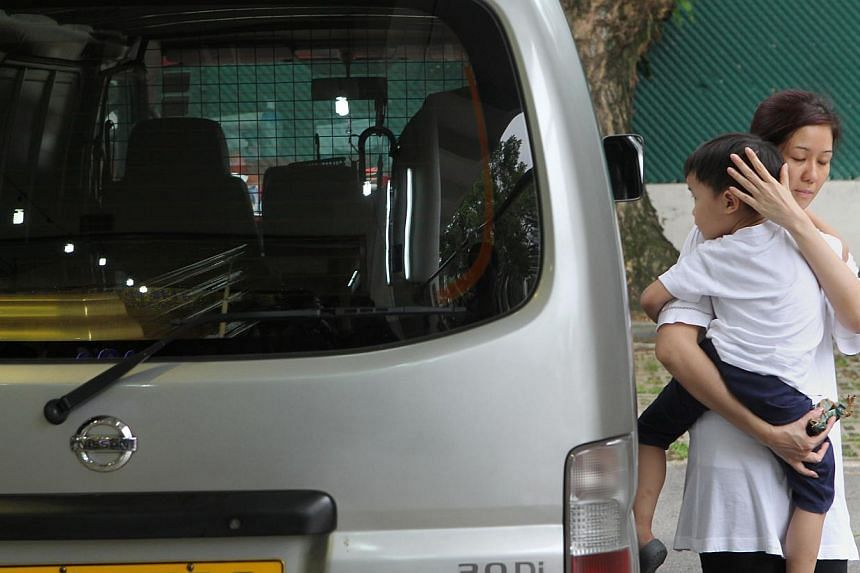 Mr Tan Chee Heong's wife with their younger son beside the hearse, as his coffin was about to be taken out at the funeral parlour yesterday.-- PHOTOS: SEAH KWANG PENG, LIANHE WANBAO