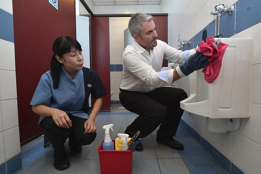 """Mr Andersch showing Ms Nan Aye Wai how to clean a urinal. Mr Andersch, who holds the title of """"cleaning excellence and development director"""" with ISS Facility Services, trains the firm's cleaners to do their jobs more efficiently, with all sess"""