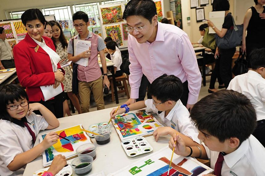 Acting Minister for Culture, Community and Youth Mr Lawrence Wong, accompanied by Bedok Green Primary principal Sita Singh (second from left), visits a batik painting class at the school on Monday, July 15, 2013. . -- ST PHOTO: MARK CHEONG