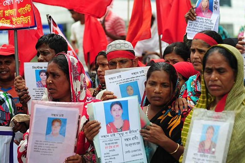 Bangladeshi garment workers, activists and relatives holding portraits of victims as they gather with others in front of the Bangladesh Garment Manufactures and Exporters Association (BGMEA) office in Dhaka on July 11, 2013. Hundreds of garment worke