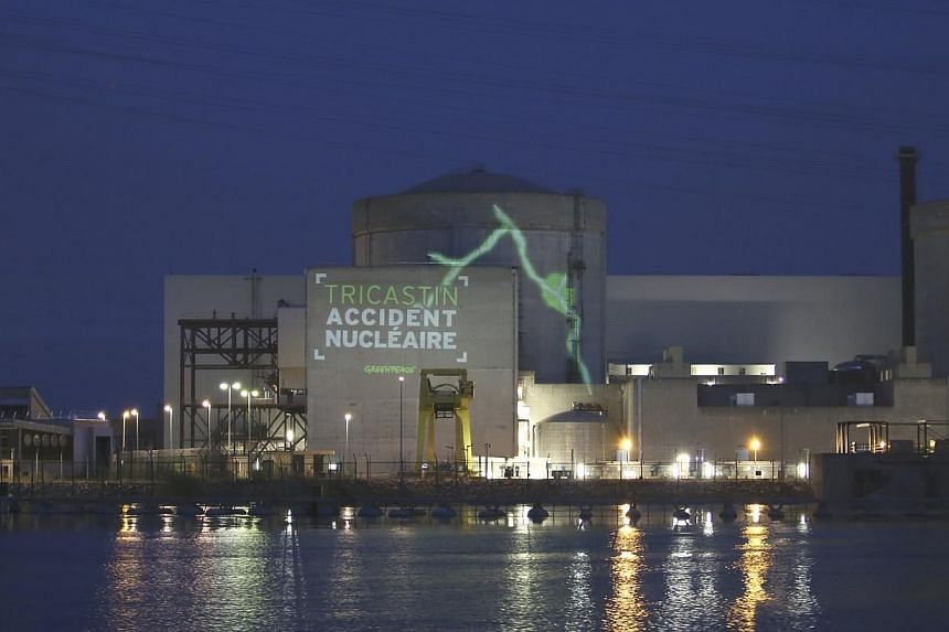 This photo provided by Greenpeace shows a video projection reading Tricastin, Nuclear Accident, President The Catastrophe, on the Tricastin power plant complex in southern France on Monday, July 15, 2013. The police on Monday arrested 29 Greenpeace a