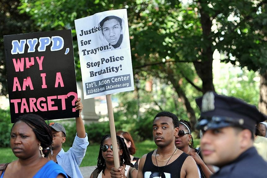 Marchers pass a New York Police Department officer (R) during a demonstration at Union Square in New York on July 14, 2013. -- PHOTO: AFP
