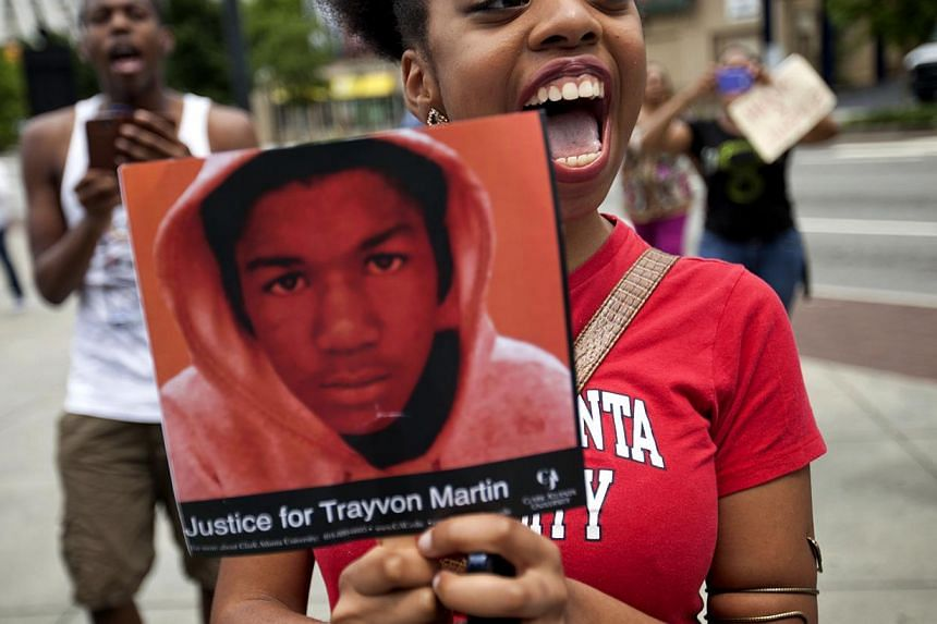 Averri Liggins, 22, of Atlanta, chants while holding a picture of Trayvon Martin during a protest the day after George Zimmerman was found not guilty in the 2012 shooting death of Martin, Sunday, July 14, 2013, in Atlanta. From New York to California