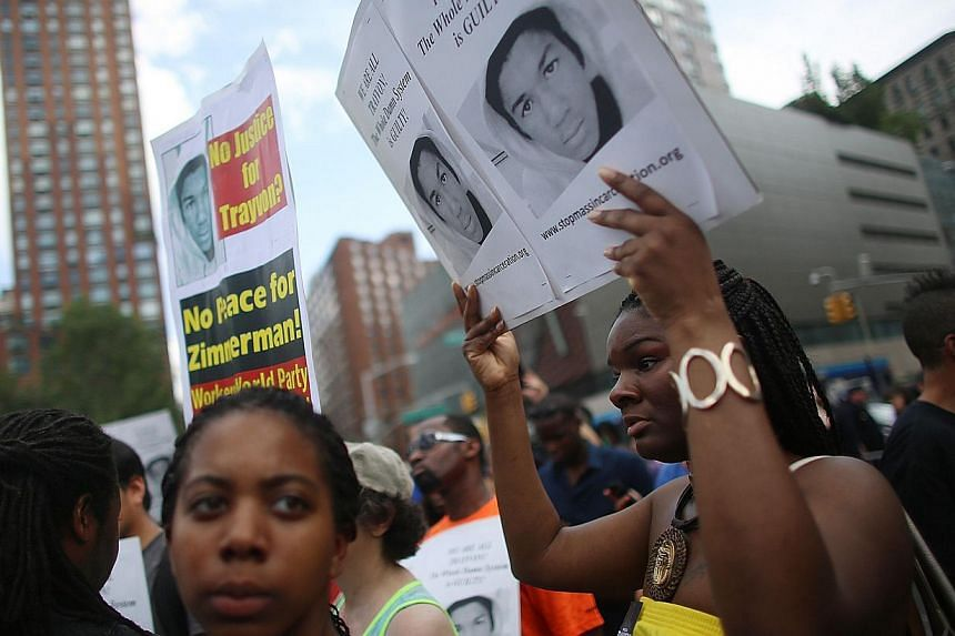 People gather at a rally honoring Trayvon Martin at Union Square in Manhattan on July 14, 2013 in New York City. George Zimmerman was acquitted of all charges in the shooting death of Martin July 13 and many protesters questioned the verdict. -- PHOT