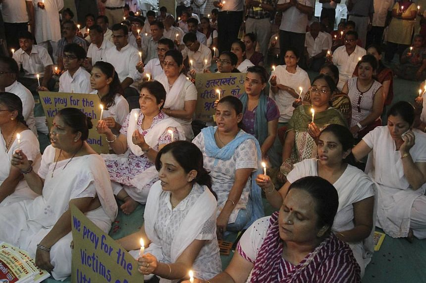 In this Tuesday, July 2, 2013 photo, Indians hold candles as they pray for the victims of Uttarakhand floods, at a temple in Ahmadabad, India. Many people are still missing in devastating floods and landslides that struck nearly a month ago in the no
