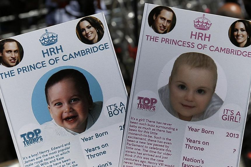 Cards depicting the 'royal baby' either as a boy or a girl, specially made by a games company as a publicity stunt are pictured, backdropped by members of the media waiting across the St. Mary's Hospital exclusive Lindo Wing in London, on Thursday, J