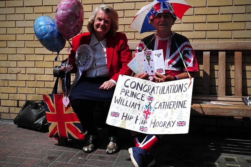 Royal well-wishers wait outside the Lindo Wing of Saint Mary's Hospital in London, on July 12, 2013, where Prince William and his wife Catherine's baby will be born. -- PHOTO: AFP