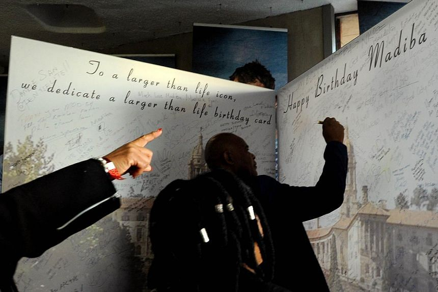 A man signs a large birthday card on July 14, 2013 at Loftus Satdium in Pretoria for ailing former South African president Nelson Mandela's upcoming July 18 birthday, after a friendly football match between Pretoria's Supersport United and Manchester