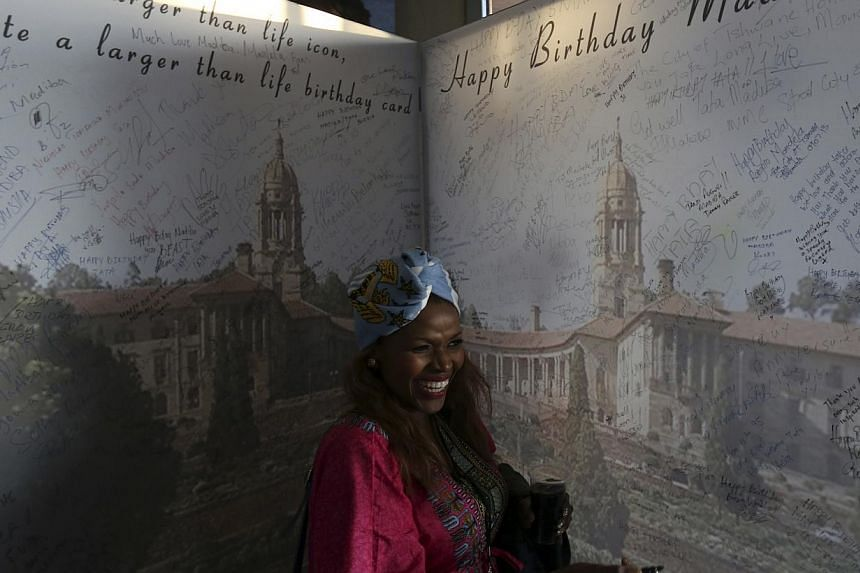 A well-wisher gestures after signing a giant birthday card for Nelson Mandela's birthday on July 18, at the end of a soccer match between Manchester City and South Africa's Supersport United in support of the Nelson Mandela Football Invitational socc