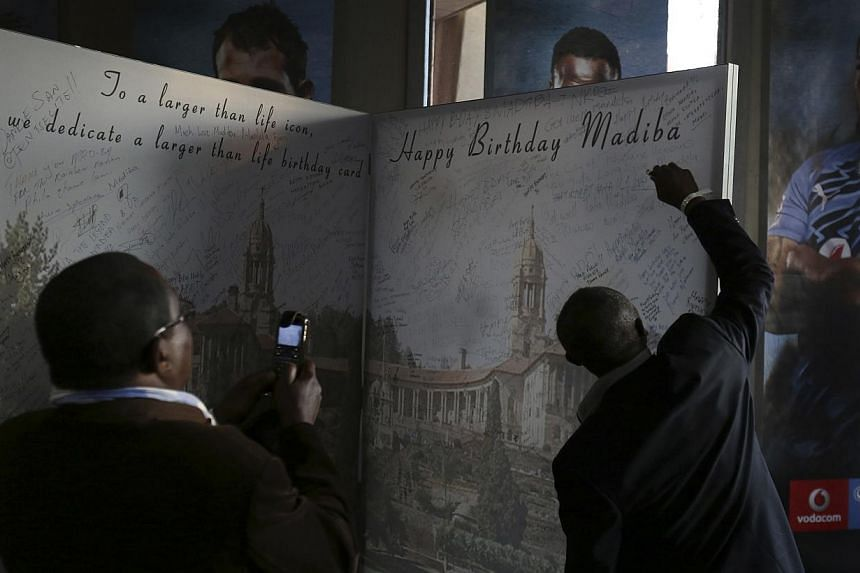 A well-wisher signs on a giant birthday card for Nelson Mandela's birthday on July 18, at the end of a soccer match between Manchester City and South Africa's Supersport United in support of the Nelson Mandela Football Invitational soccer at Loftus V