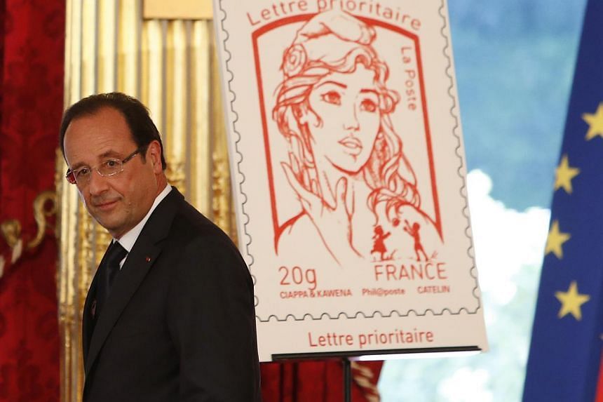 French President Francois Hollande stands next to the newly unveiled official Marianne postal stamp at the Elysee Palace during the Bastille Day celebrations in Paris on July 14, 2013.  The postage stamp depicting France's cultural symbol has to