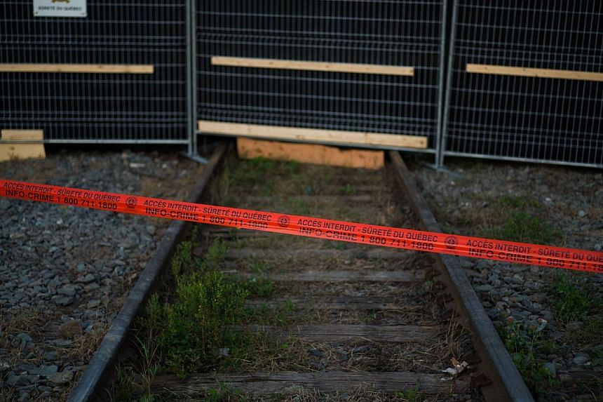"""Police tape marks the outside boundary of the """"red zone"""" crash site on July 14, 2013 in Lac-Megantic, Quebec, Canada.Two residents of the Quebec town of Lac-Megantic, where a runaway train derailed on July 6 and exploded into a wall of fire tha"""