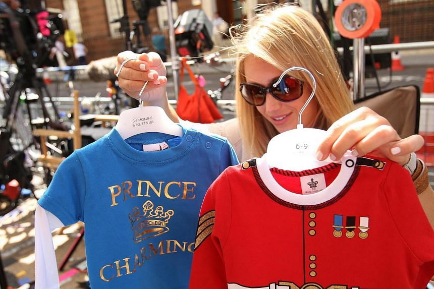 A member of the US media decides which baby clothes to show to the camera outside the Lindo Wing of St Mary's Hospital, where Britain's Catherine, Duchess of Cambridge is due to give birth, in London on July 15, 2013. -- PHOTO: REUTERS