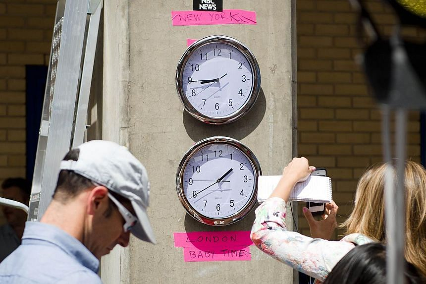 "Clocks showing New York and ""London Baby Time"" are hung on a wall in the media pen outside the Lindo Wing of Saint Mary's Hospital in London, on July 15, 2013, where Prince William and his wife Catherine's baby will be born. -- PHOTO: AFP"